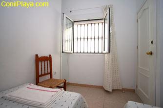 El dormitorio tiene ventana al exterior y un pequeño armario empotrado con espejo a la izquierda.