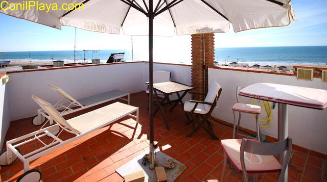 Terraza con tumbonas y mesas