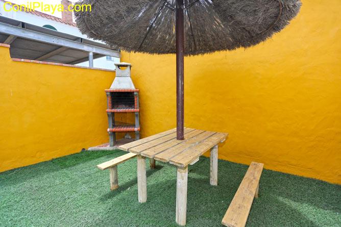 barbacoa y mesa con sombrilla