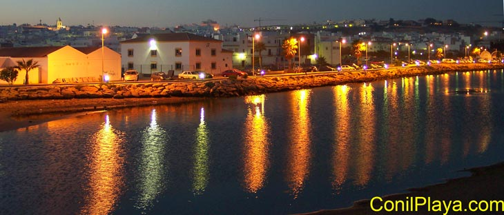 Foto nocturna de Conil realizada desde el puente del rio salado con marea alta.