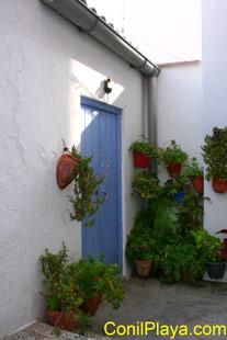 Puerta de una casa tradicional de Conil adornada con geranios.
