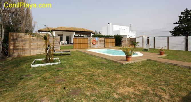 piscina, jardín y al fondo la casa