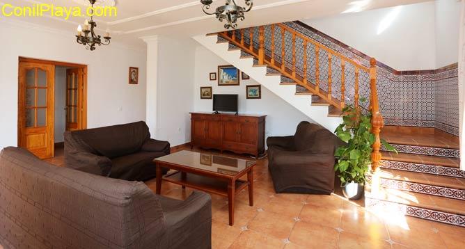 Vista del salón con el sofá y escaleras al fondo