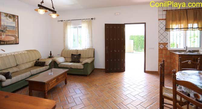 vista del salón con sofá, al fondo la puerta de entrada