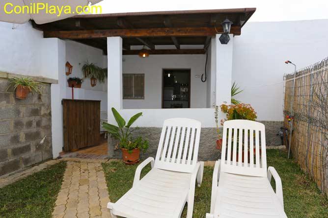 jardin con tumbonas y ducha y el porche al fondo