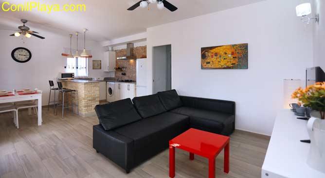 salón con sofa chaise-longue y al fondo el comedor y la cocina