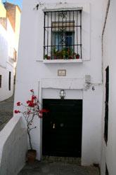 Casa típica de Vejer con el balcón repleto de macetas con geranios.
