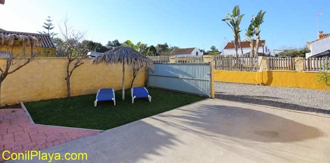 patio con tumbona y sombrilla en jardin con césped